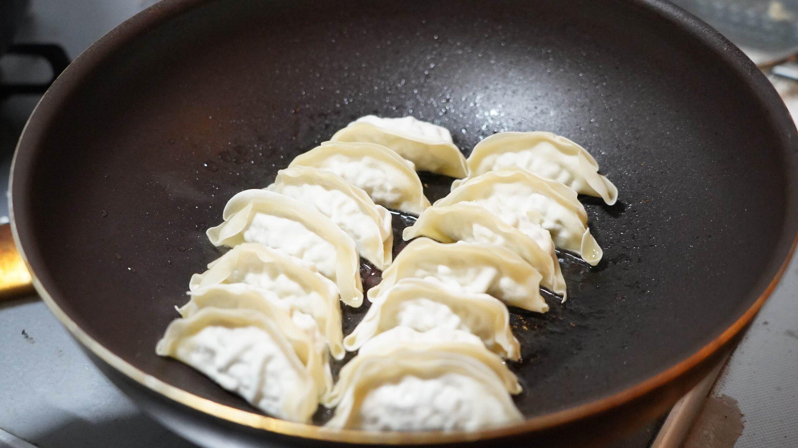 生協宅配限定の冷凍餃子「香港ギョーザ」をフライパンで焼いている写真