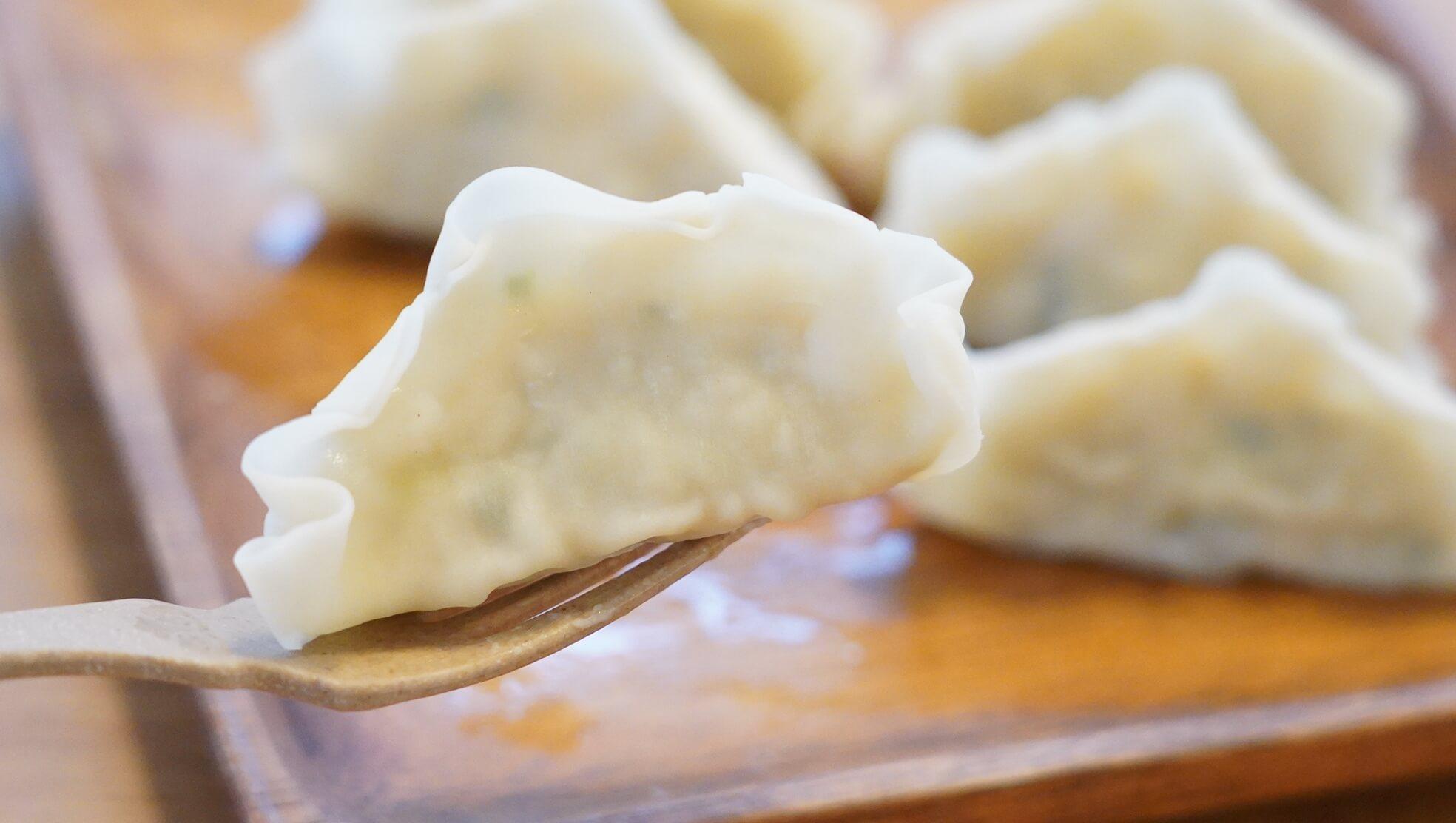 冷凍食品「マッスル餃子」をフォークで持ち上げている写真