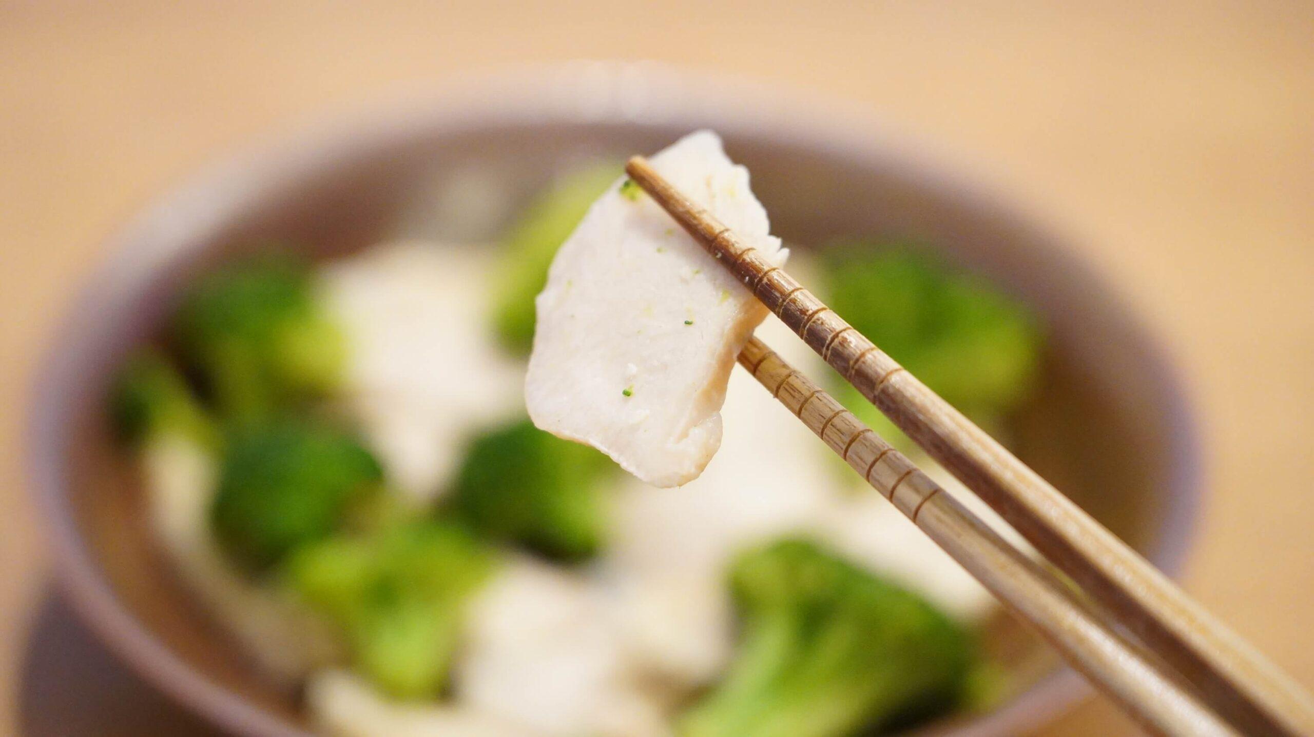 セブンイレブンの冷凍食品「鶏むね肉とブロッコリー」の鶏肉を箸で持ち上げている写真