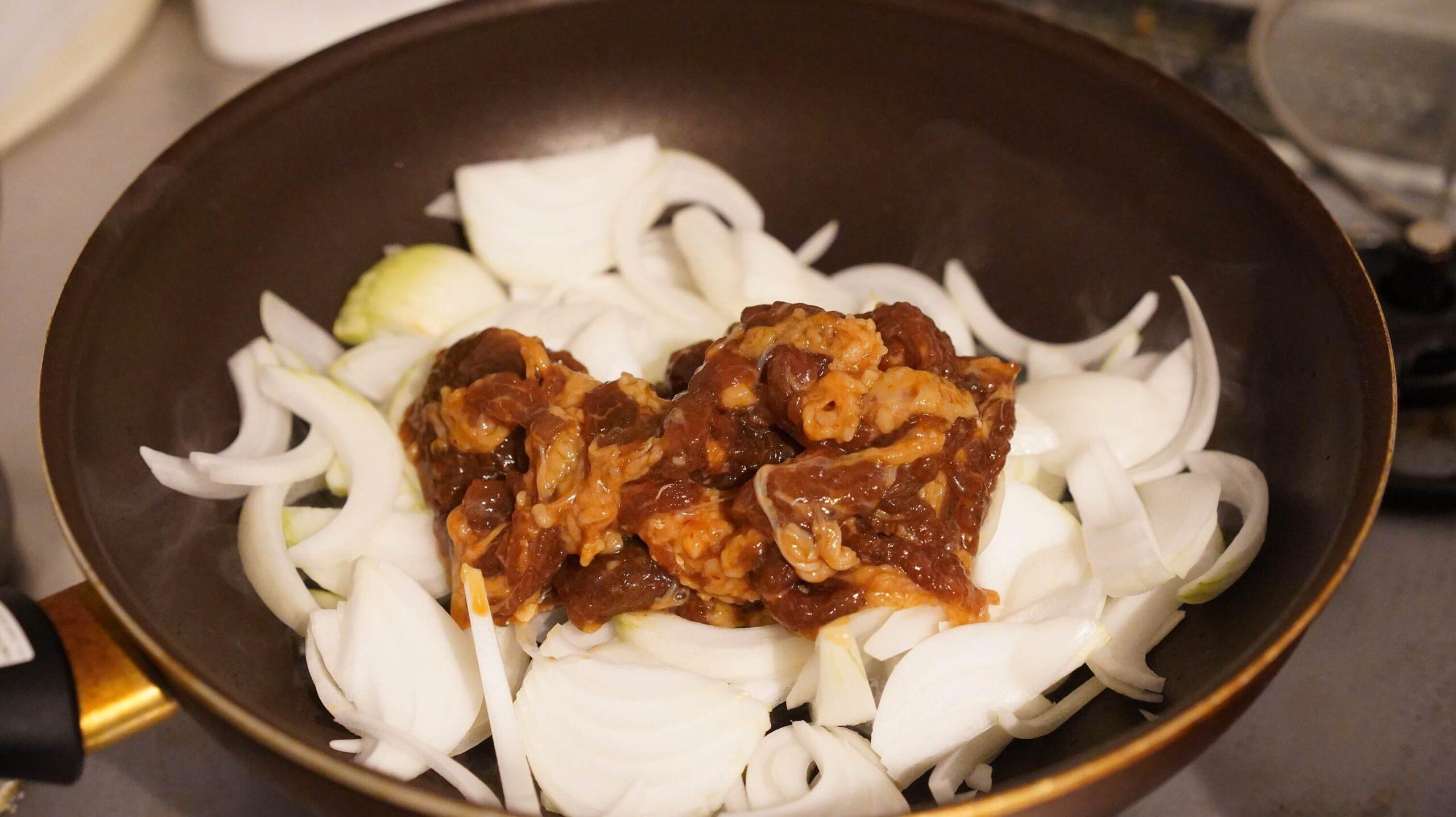 青森のB級グルメ「十和田バラ焼き」の冷凍食品をフライパンで炒めている写真