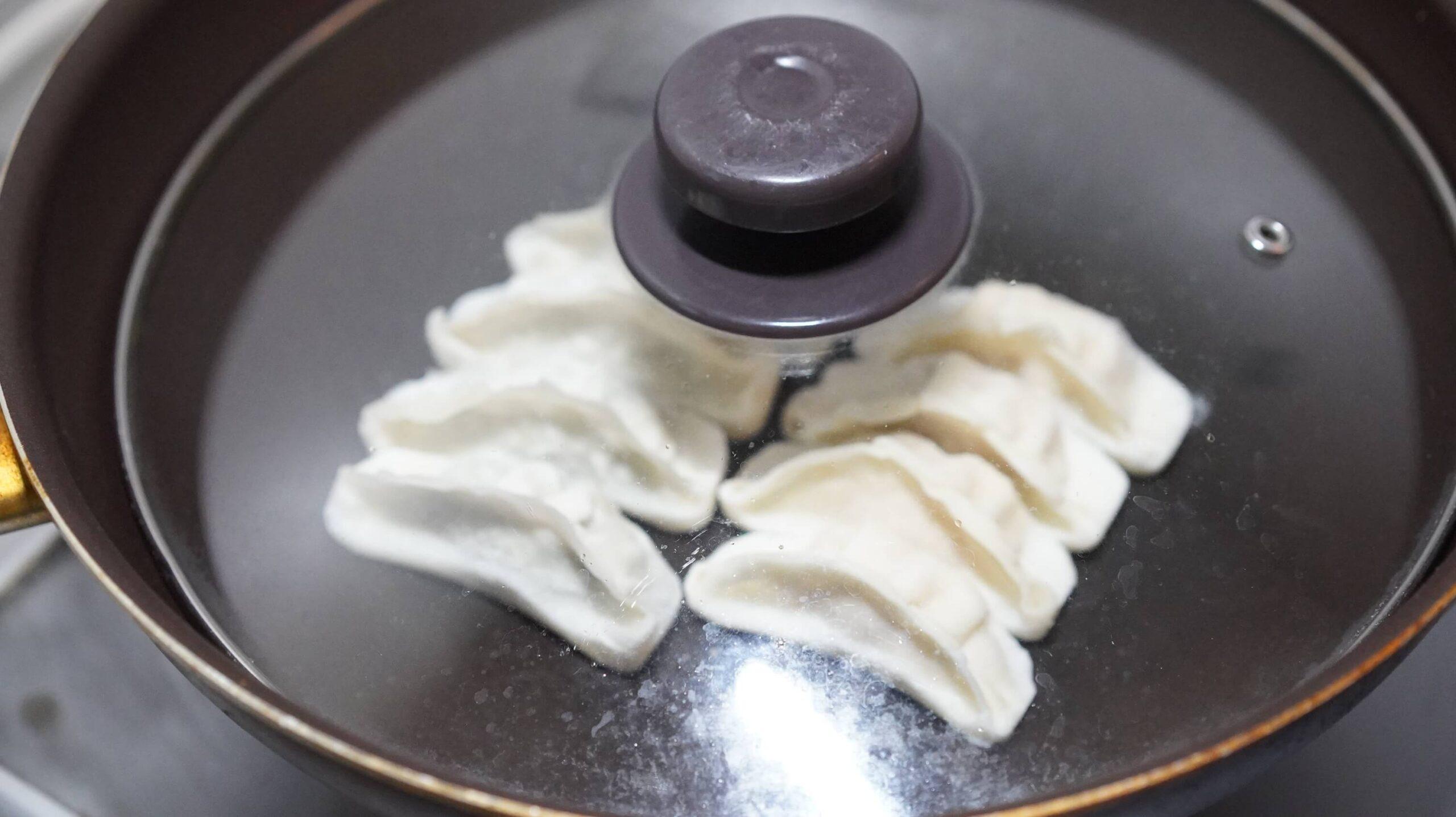 味の素のアスリート専用の冷凍餃子「コンディショニングギョーザ」をフライパンで焼いている写真