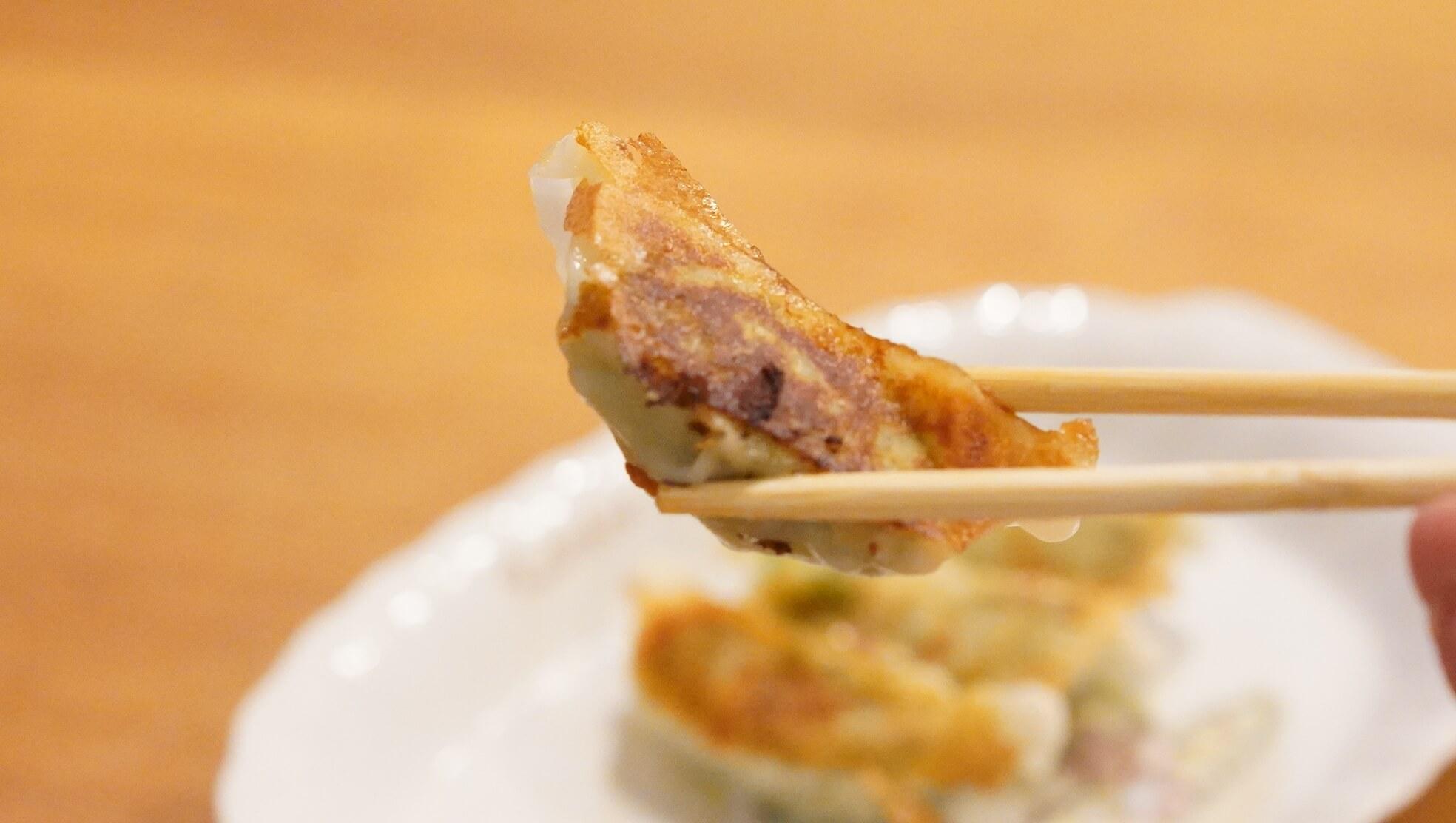 味の素のアスリート専用の冷凍餃子「コンディショニングギョーザ」を箸でつまんだ写真
