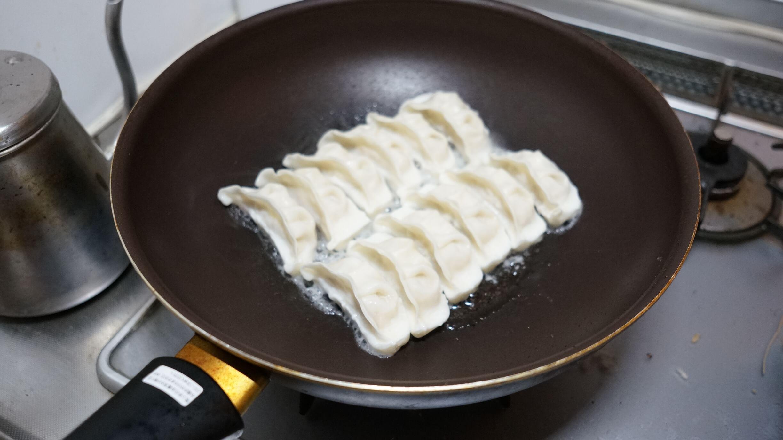 味の素の冷凍食品の餃子「米粉でつくったギョーザ」をフライパンで焼いている写真