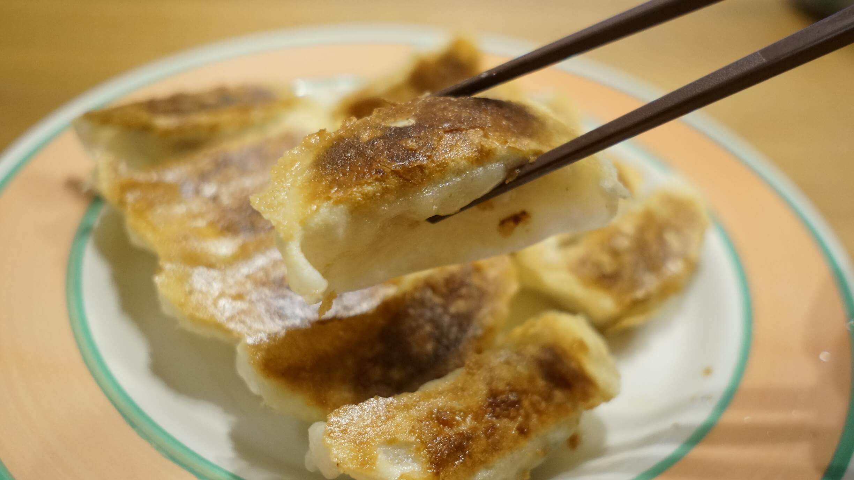 味の素の冷凍食品の餃子「米粉でつくったギョーザ」を箸でつまんでいる写真