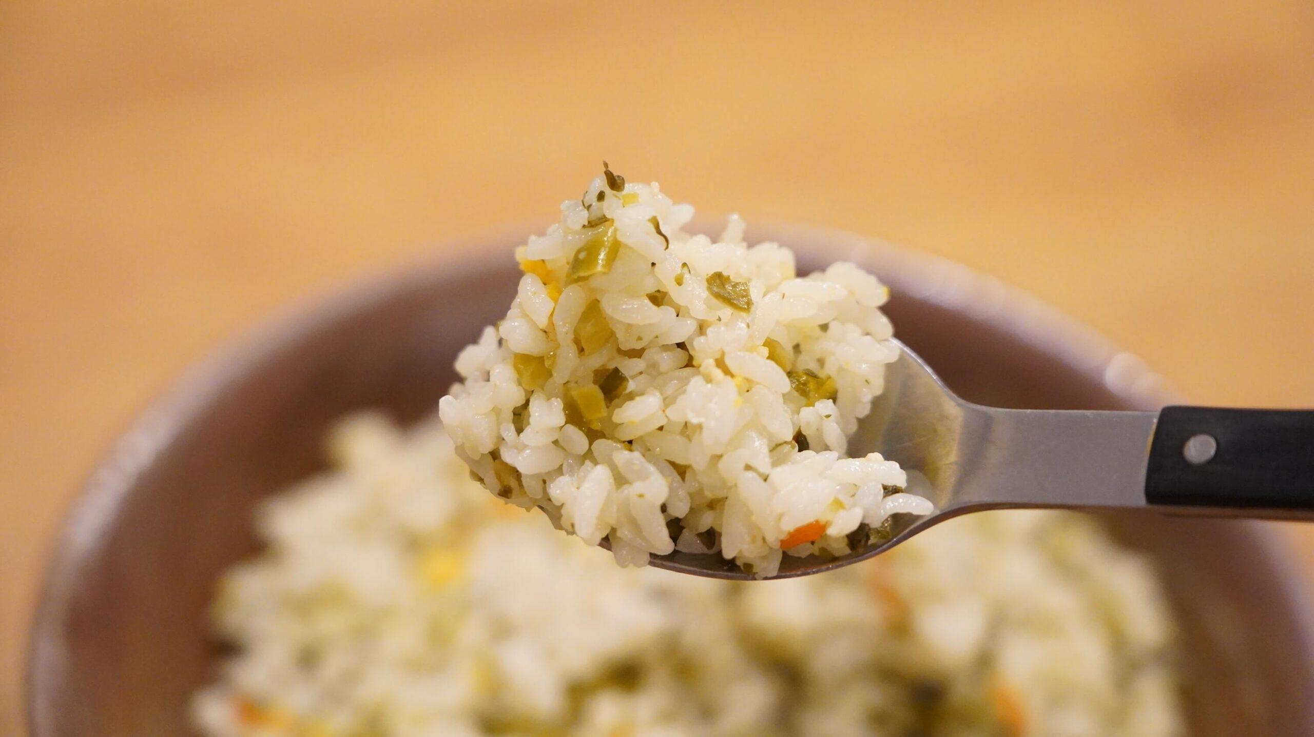 イオン(トップバリュ)の冷凍食品「高菜ピラフ」をスプーンですくっている写真