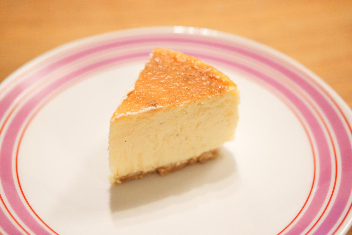 通販で買える美味しいホール・チーズケーキ「東京・代々木上原ミシュラン一つ星フレンチsio鳥羽周作シェフ」の絶品チーズケーキを皿に盛り付けた写真